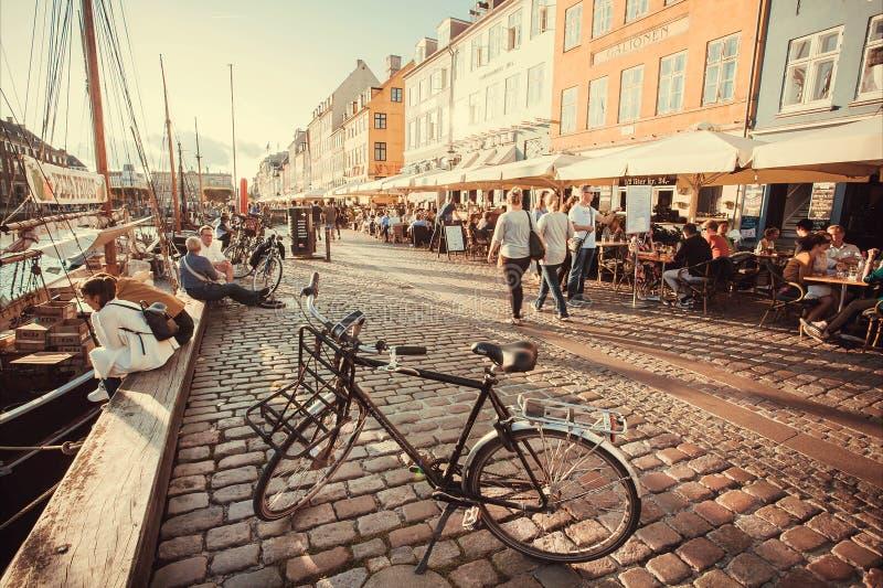 Avondzon op Nyhavn riverbank met lopende mensen, en het ontspannen in restaurants van het populaire gebied van de stadsvrije tijd stock fotografie