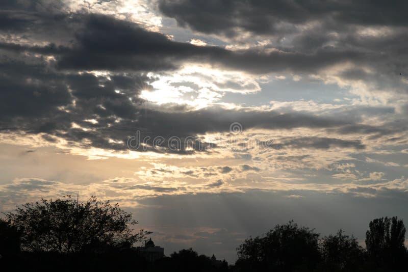 Avondzonsondergang in de stad De stralen van de zon maken hun manier door de wolken stock foto's
