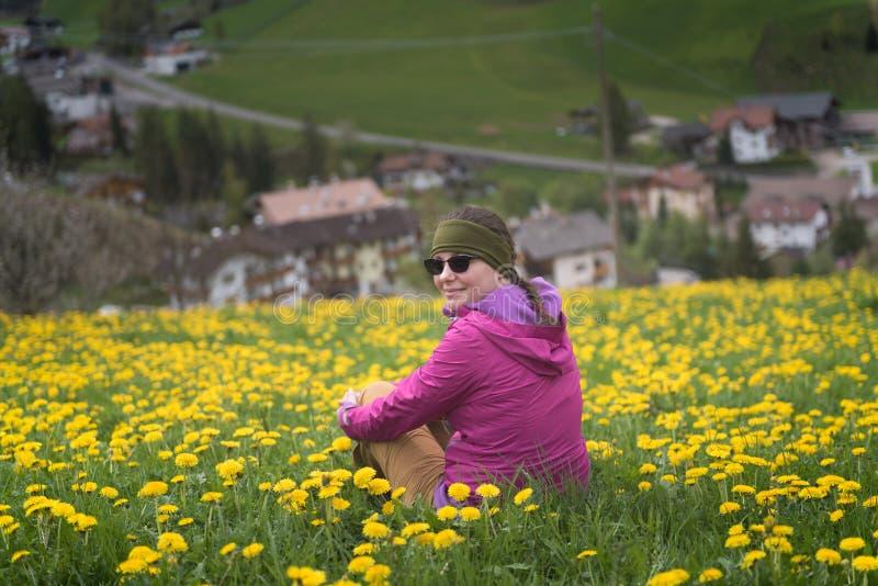 Avonturenvrouw die een rust op paardebloemengebied hebben na een stijging, Dolomiet royalty-vrije stock afbeeldingen