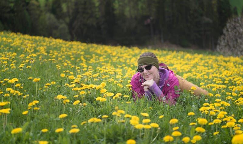 Avonturenvrouw die een rust op paardebloemengebied hebben na een stijging, Dolomiet stock foto