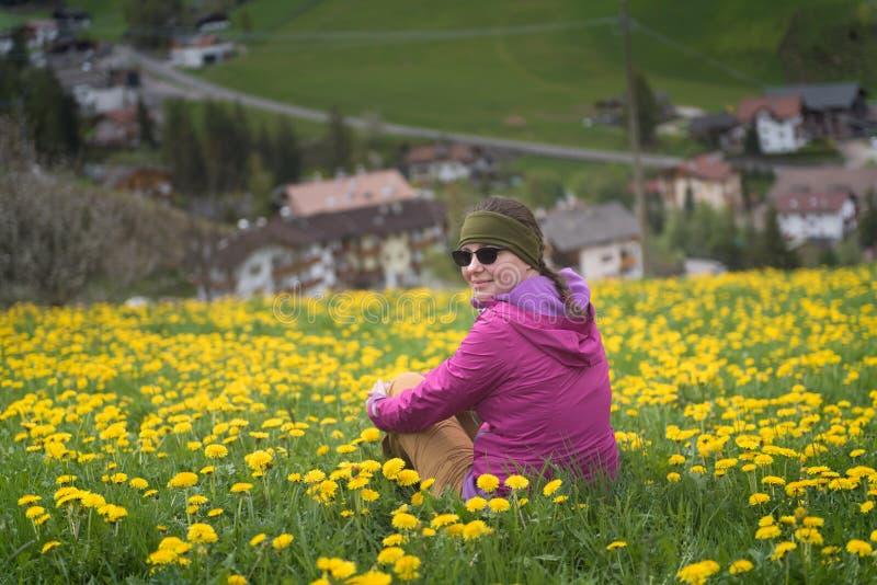 Avonturenvrouw die een rust op paardebloemengebied hebben na een stijging, Dolomiet stock afbeeldingen