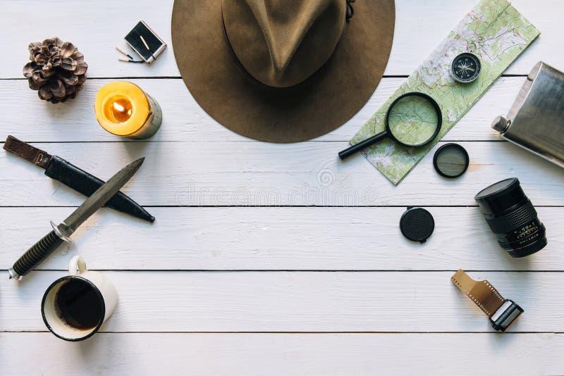 Avontuur de planningsvlakte lag Reis uitstekend toestel op witte houten lijst Met inbegrip van filmcamera, omringt de hoed, mes,  stock afbeelding