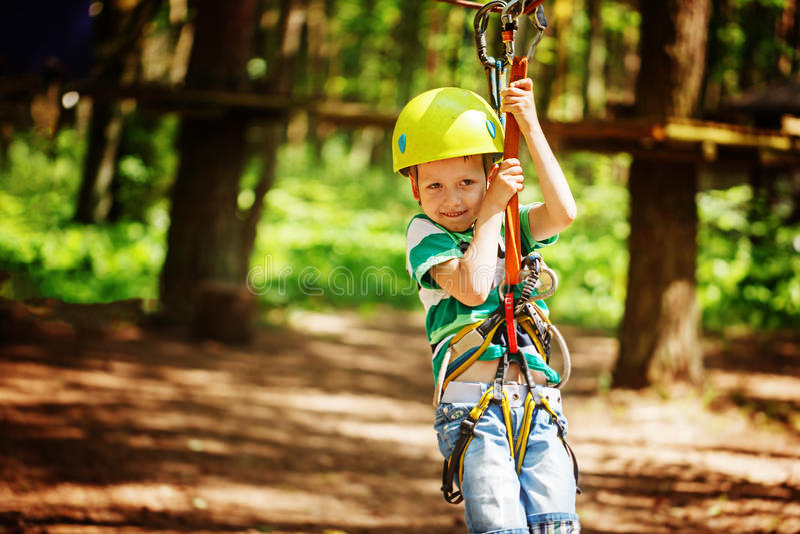Avontuur die hoog draadpark beklimmen - weinig kind op cursus in berghelm en veiligheidsmateriaal stock afbeeldingen