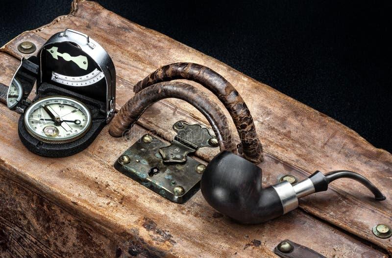 Avontuur en reis met kompas, koffer en pijp, het wachten trein voor reis aan exotische plaatsen stock fotografie