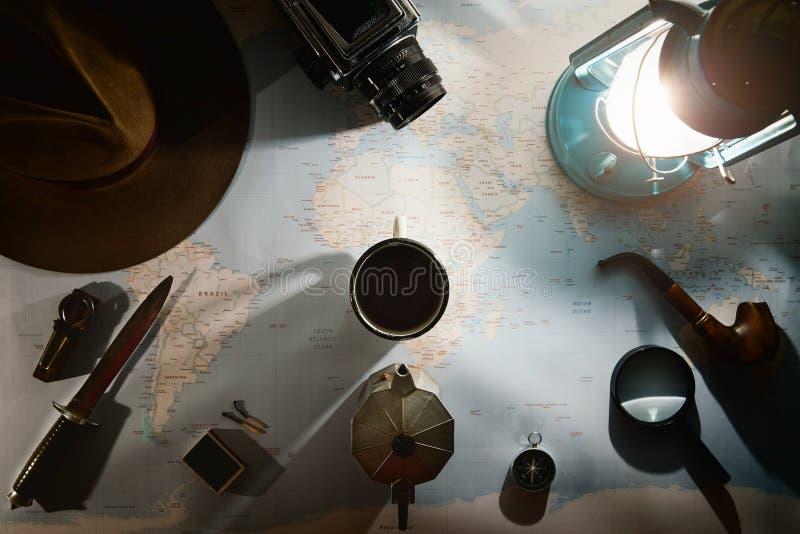Avontuur planning dichtbij de vlakte van de gaslamp lag Atmosferisch oud toestel op kaart De reiziger, ontdekkingsreiziger dient  stock foto