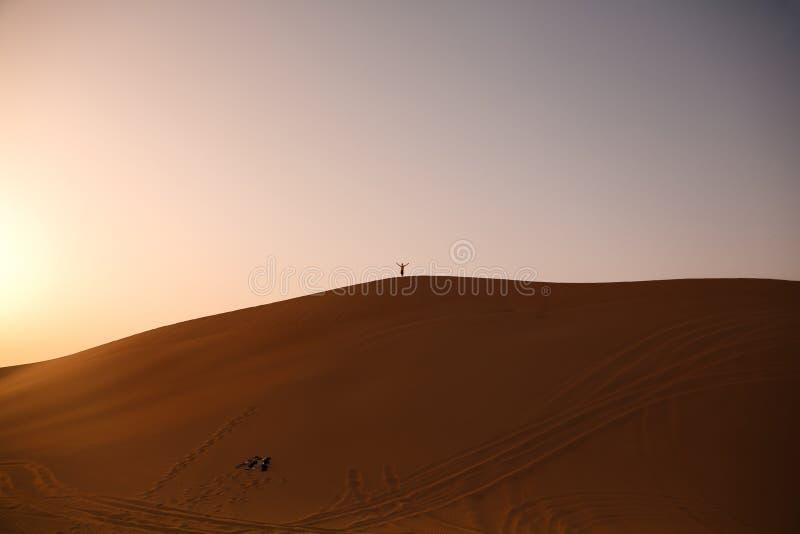Avontuur, reis of actief extreem vakantieconcept: het snowboarding in de woestijn Cijfers van mensen bovenop het duin stock fotografie