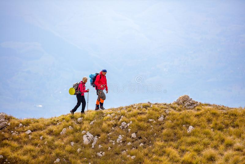 Avontuur, reis, toerisme, stijging en mensenconcept - glimlachend paar die met rugzakken in openlucht lopen stock afbeelding