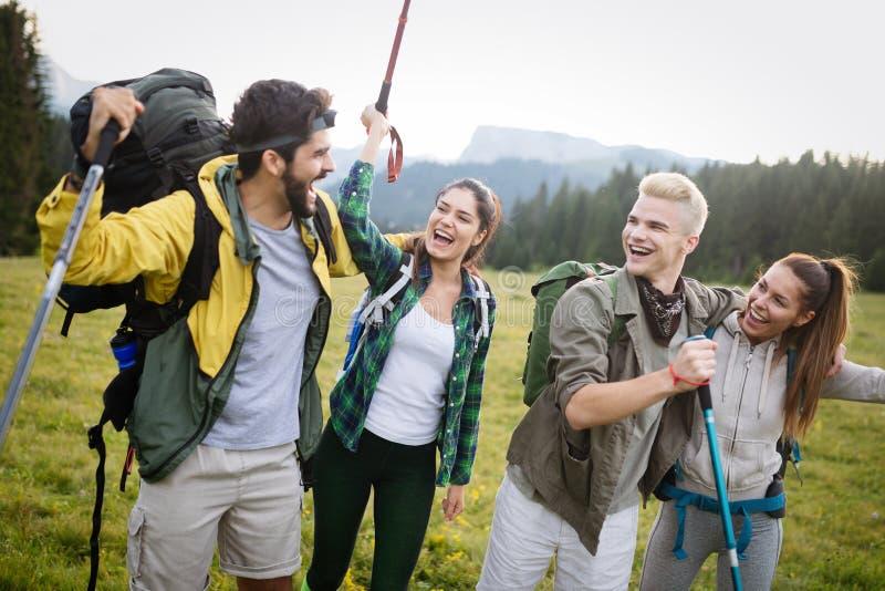 Avontuur, reis, toerisme, stijging en mensenconcept - groep glimlachende vrienden met rugzakken en kaart in openlucht stock foto's