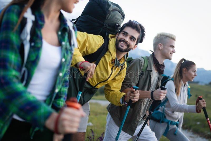 Avontuur, reis, toerisme, stijging en mensenconcept - groep glimlachende vrienden met rugzakken en kaart in openlucht royalty-vrije stock foto