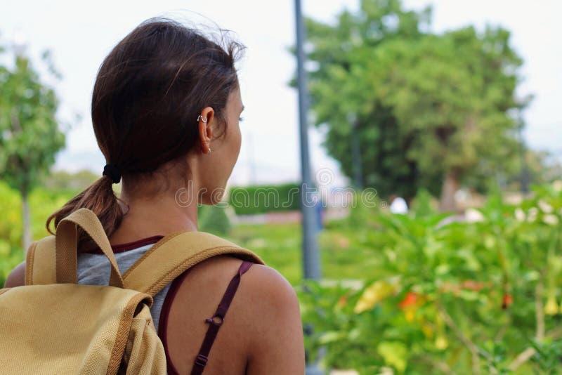 Avontuurlijk meisje met een gele wandelingsrugzak die aard bekijken stock afbeeldingen