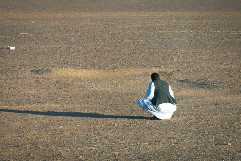 Avril 2019 Homme musulman s'asseyant dans le désert image stock
