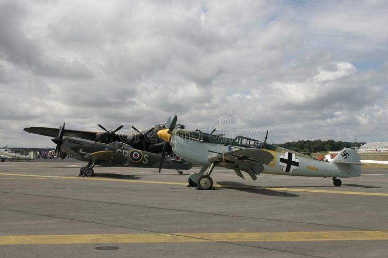 Avro Lancaster, Messerschmitt BF109 and Spitfire Mk14 at Farnborough. Cloud and sun with Lancaster behind the fighters royalty free stock photography