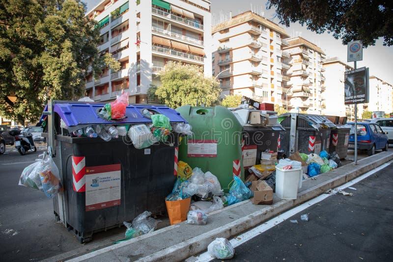 Avskräde slänga i soptunnan av rackar ner på mycket, bland gatorna och byggnaderna av staden royaltyfri foto