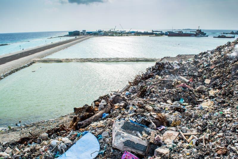 Avskrädeförrådsplatsen nära havstranden mycket av rök, kull, plast-flaskor, rackar ner på och kasserar på den tropiska ön royaltyfri foto