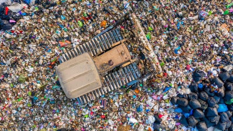Avskrädehögen i avfallförrådsplats eller nedgrävning av sopor, avskrädelastbilar för den flyg- sikten lastar av avskräde till en  royaltyfria foton