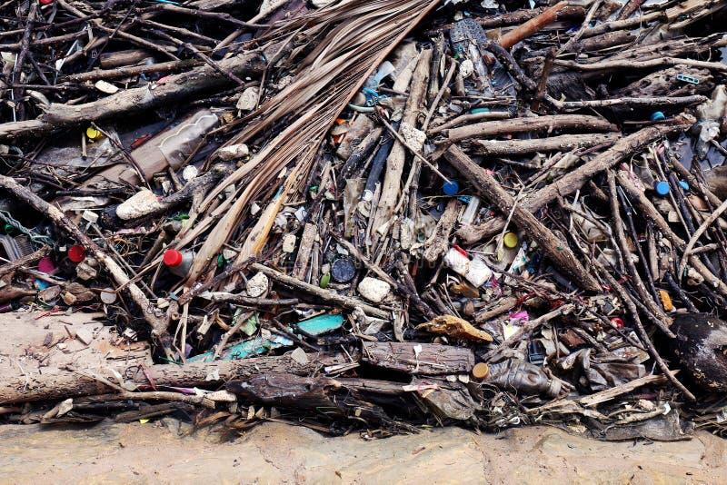 Avskrädehöginsättningen förgrena sig trä, högen av trä och plast- flaskor avfalls och skräp som svävar på vattenyttersida på flod arkivbild