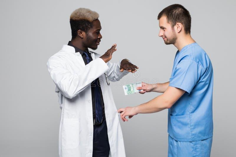 Avskräden för medicinsk doktor som muter pengar från kirurgen som isoleras på grå bakgrund fotografering för bildbyråer