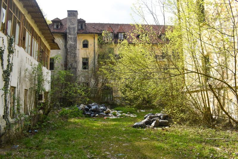 Avskrädepåsar lämnade i den övergav grannskapen arkivfoton