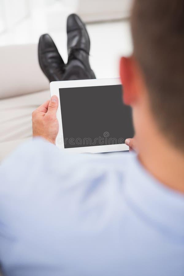 Avslappnande affärsman på en soffa med en minnestavla royaltyfria foton