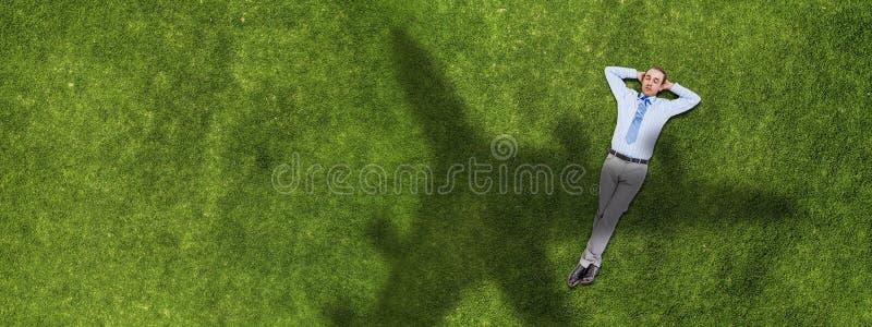 Avslappnande affärsman på gräs arkivfoton