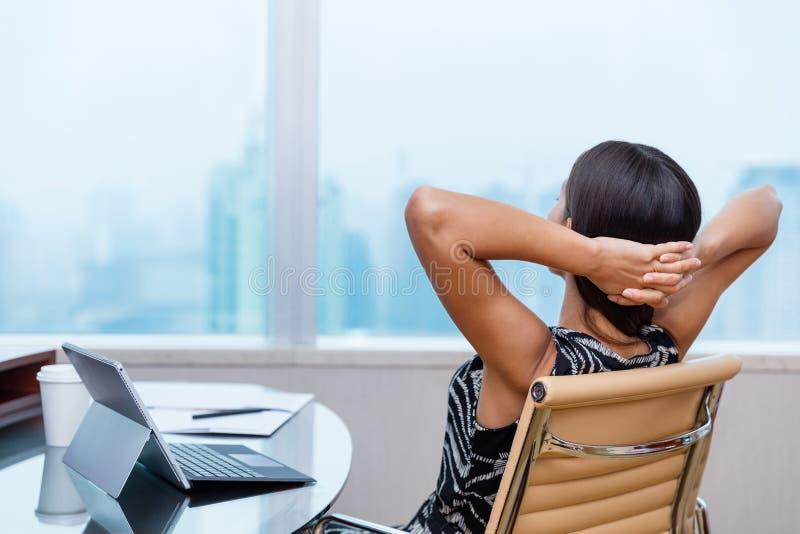 Avslappnande arbete för affärskvinna på kontorsskrivbordet royaltyfri foto