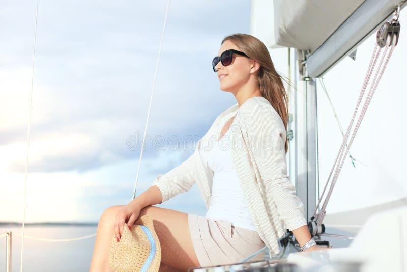 Avslappnande attraktiv ung kvinna på semestersammanträde på yachten arkivbilder