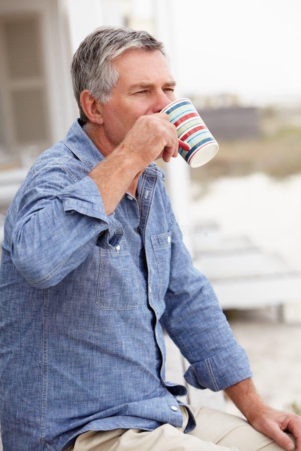 Avslappnande det fria för hög man som dricker kaffe royaltyfria bilder