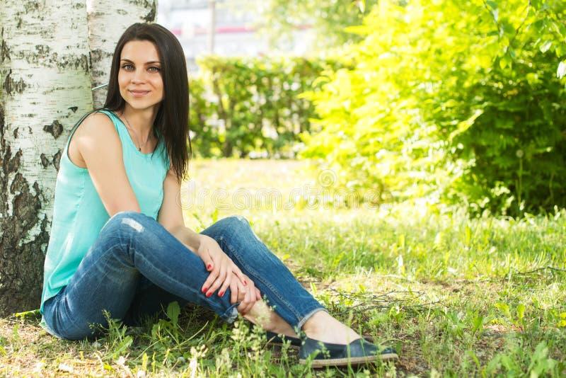 Avslappnande det fria för kvinna på gräs och att le arkivfoto