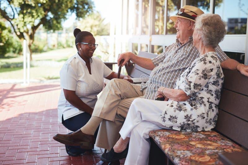 Avslappnande det fria för pensionerade par med den kvinnliga anhörigvårdaren royaltyfri fotografi