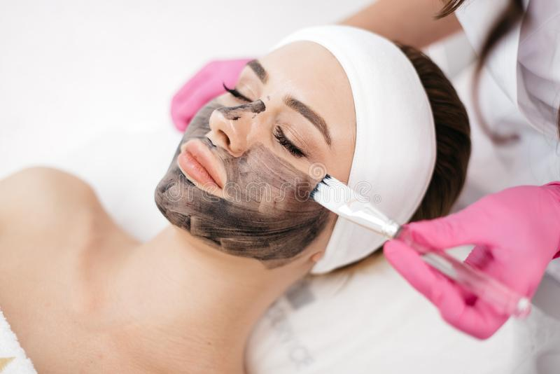 Avslappnande härlig kvinna med naturligt smink i brunnsortsalongen Händerna av kosmetologen som applicerar den svarta maskeringen arkivbild