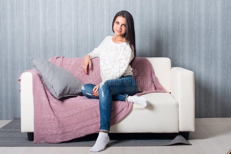 Avslappnande hemmastatt, komfort gullig ung kvinna som ler och att koppla av på den vita soffan, soffa arkivbild