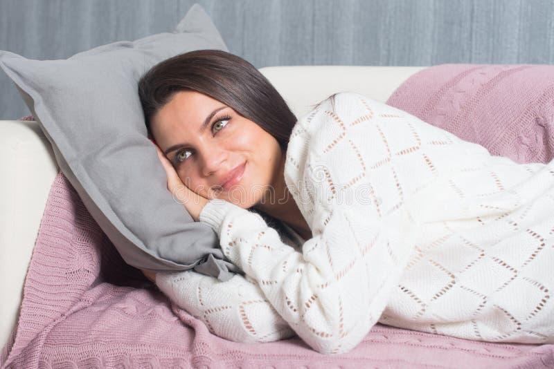 Avslappnande hemmastatt, komfort gullig ung kvinna som ler och att koppla av på den vita soffan, soffa hemma fotografering för bildbyråer