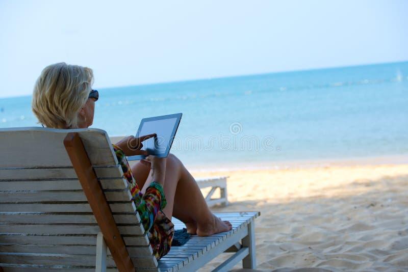 Avslappnande kvinna i solvardagsrum arkivfoto