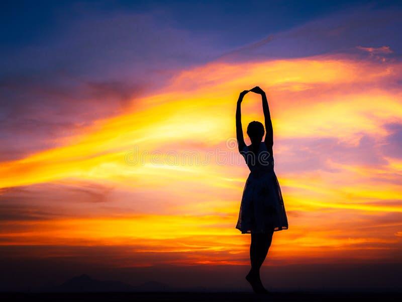 avslappnande kvinna på solnedgången arkivfoto