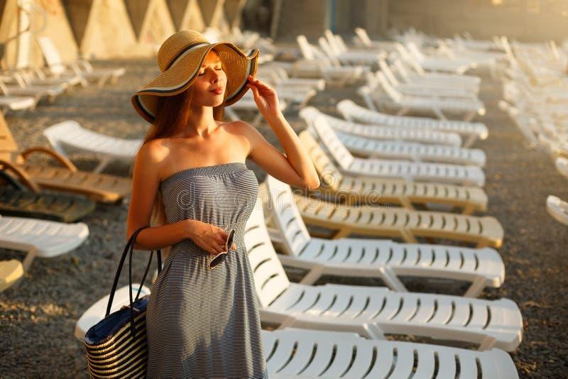 Avslappnande kvinna som tycker om det lyckliga anseendet för sommarsol i en bred solhatt på stranden med framsidan som lyfts till royaltyfria bilder