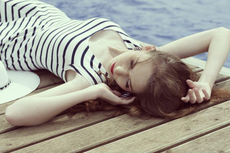 Avslappnande moderiktig flicka i sommartid arkivfoto