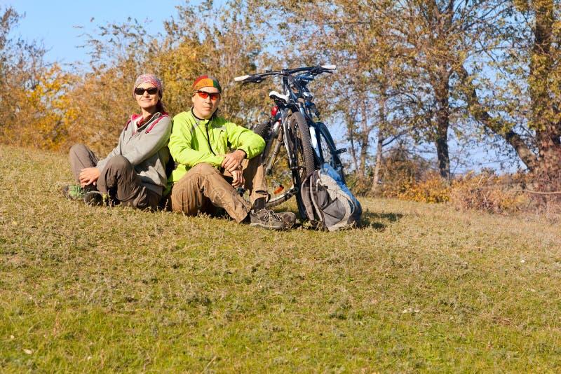 Avslappnande mountainbikepar utomhus arkivbild