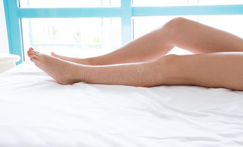 Avslappnande och lycklig tid för Closeupkvinnafot på vit säng-, skönhet- och hälsovårdbegreppsbakgrund, kopieringsutrymme, åtlöje royaltyfria bilder