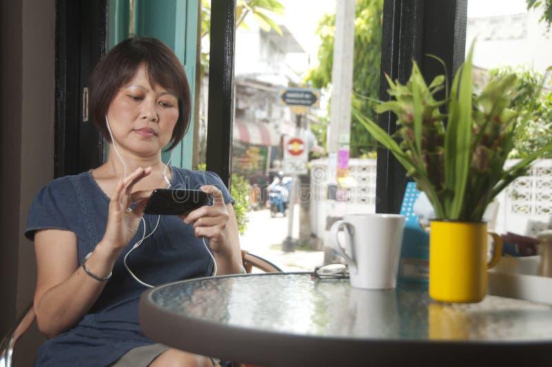 avslappnande smartphonekvinna för asiatisk cafe royaltyfri fotografi