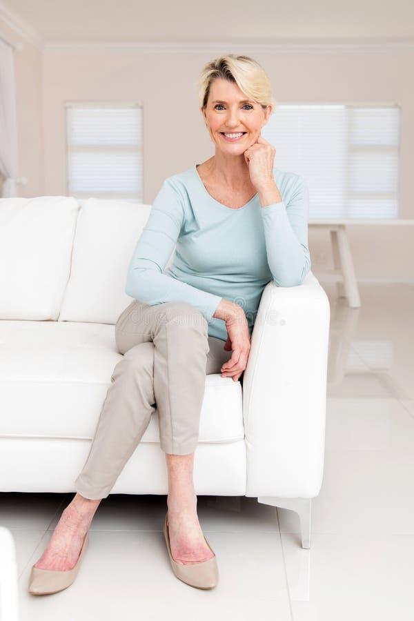 Avslappnande soffa för hög kvinna arkivfoto