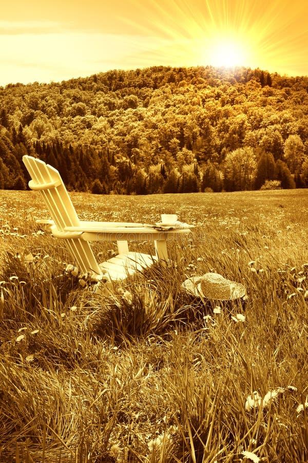 avslappnande sommarsolnedgång för stol royaltyfri bild