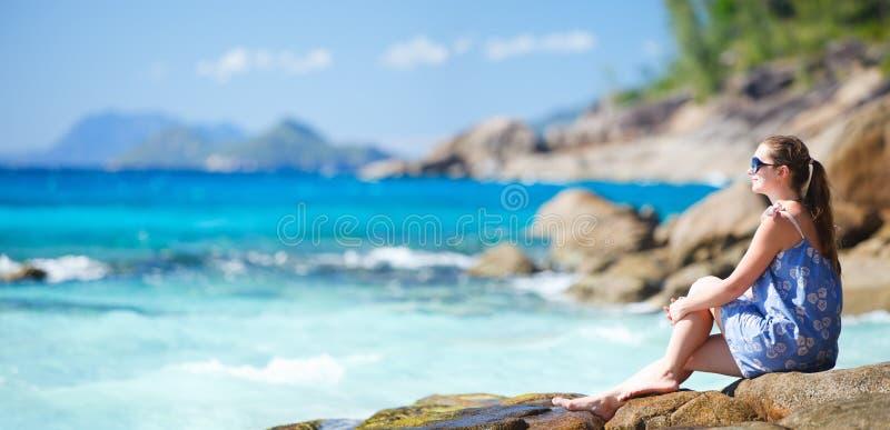 avslappnande stenigt kvinnabarn för kust arkivfoto
