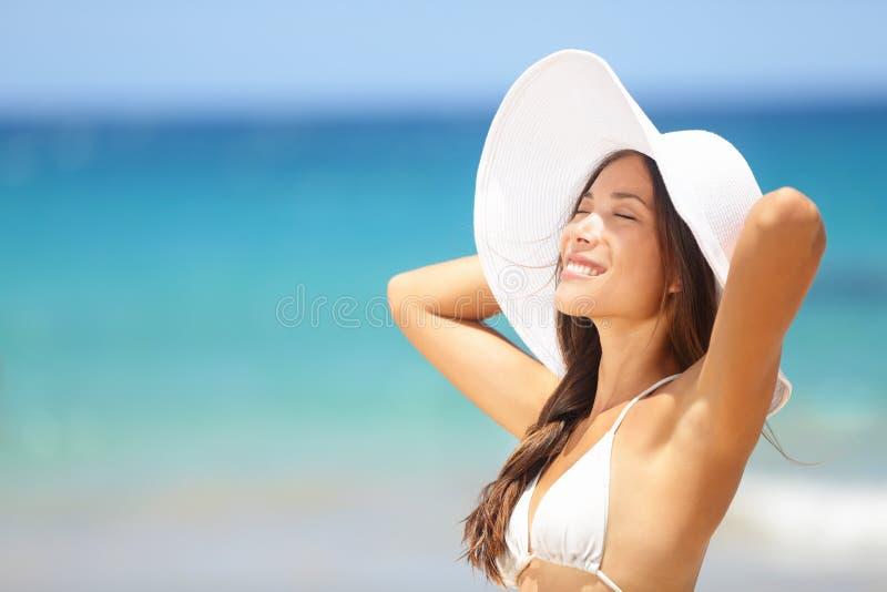 Avslappnande strandkvinna som tycker om den lyckliga sommarsolen royaltyfri foto