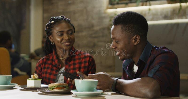Avslappnande svart man och kvinna i kafé royaltyfri bild