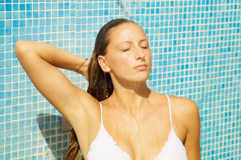 Avslappnande tagande dusch för blond kvinna i yttersida i sommar royaltyfria bilder