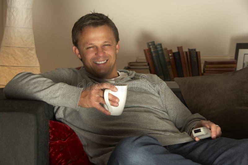 avslappnande television för kaffeman fotografering för bildbyråer