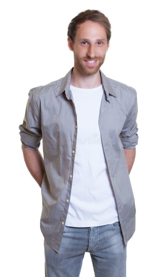 Avslappnande tysk grabb i grå skjorta med skägget i jeans royaltyfri fotografi