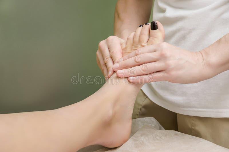 Avslappnande yrkesmässig massage på den kvinnliga foten i salongen arkivfoto