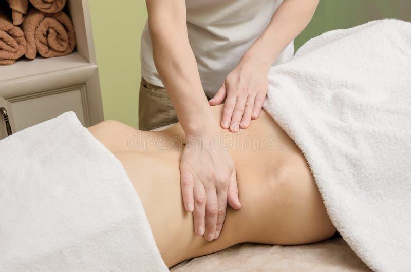Avslappnande yrkesmässig massage på den kvinnliga magen i salongen royaltyfria foton