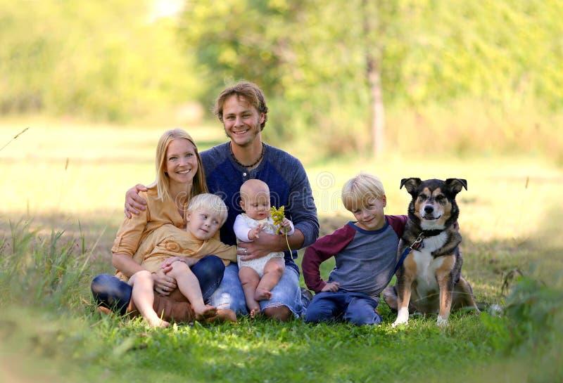 Avslappnande yttersida för lycklig ung familj med den älsklings- hunden royaltyfri fotografi